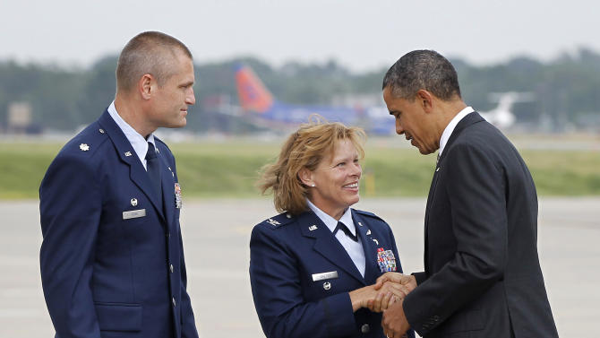 President Barack Obama, right, is greeted by Col. Jennifer Walter, center, Vice Wing Commander, Iowa Air National Guard and Lt. Col. Shawn Ford, Operation Group Commander, Iowa Air National Guard Base, upon his arrival at Des Moines International Airport, Thursday, May 24, 2012, in Des Moines, Iowa. (AP Photo/Pablo Martinez Monsivais)