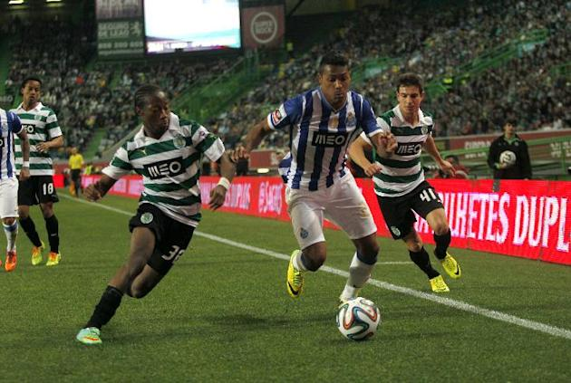Porto's Alex Sandro, center, from Brazil, tussles for the ball with Sporting's Cedric Soares, right, and Carlos Mane during the Portuguese league soccer match between Sporting and Porto at Spo