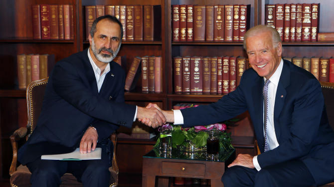 US Vice President Joe Biden, right, and Sheikh Moaz al-Khatib, Syria's  top opposition leader, shake hands at the Security Conference in Munich, southern Germany, on Saturday, Feb. 2, 2013.  (AP Photo/Matthias Schrader)