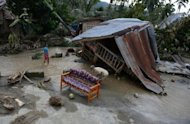 Residents clean up next to their damaged house in New Bataan town on December 5. Manila has appealed for international assistance after a deadly typhoon killed 477 people left a quarter of a million homeless
