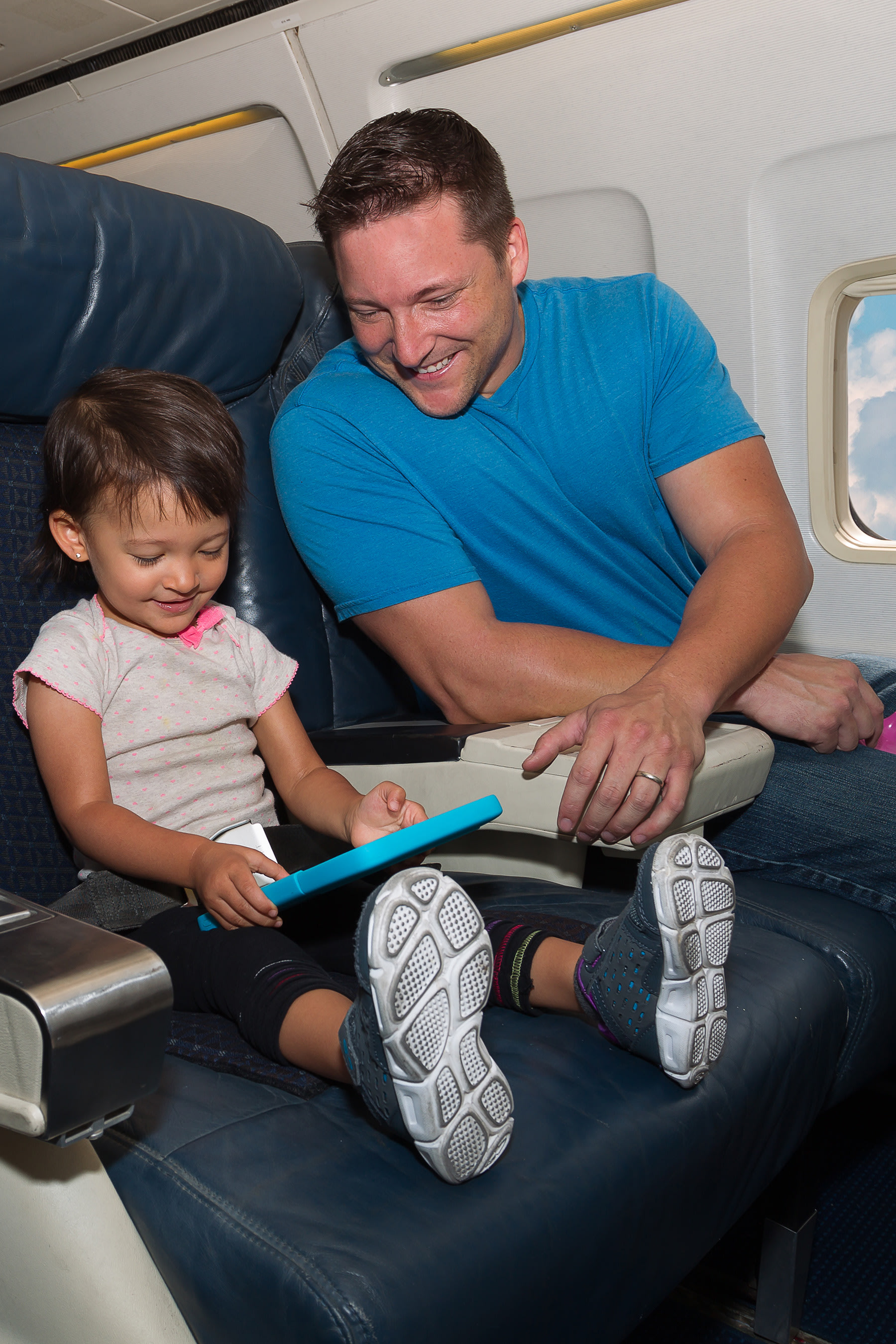 Little girl playing on tablet with father in cabin