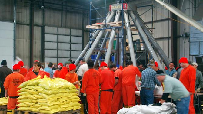 FILE - In this Feb. 14, 2011 file photo inmates from the Cass County jail help at the sandbag filling machine in Fargo, N.D., as preparations begin for Red River flooding. Fargo officials say they plan to make 500,000 sandbags to add to a reserve of 750,000 bags following  the National Weather Service warning Thursday, March 21, 2013 that Red River residents Fargo and neighboring Moorhead, Minn., should prepare for one of the top five floods in their history. (AP Photo/Dave Kolpack, File)