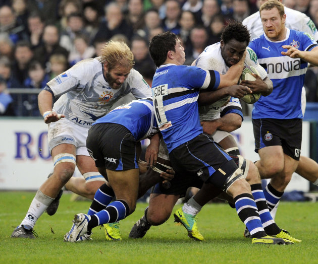 CORRECTS IDENTITY Bath's Francois Louw, centre, and Olly Woodburn, 2nd left, tackle Montpellier's Fulgence Ouedraogo during their Heineken Cup pool 3 rugby match at the Recreation ground, Bath, Englan