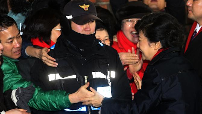 South Korea's presidential candidate Park Geun-hye of the ruling Saenuri Party shakes hands with a supporter as she leaves her home to head to her office in Seoul, South Korea, Wednesday, Dec. 19, 2012. (AP Photo/Yonhap) KOREA OUT