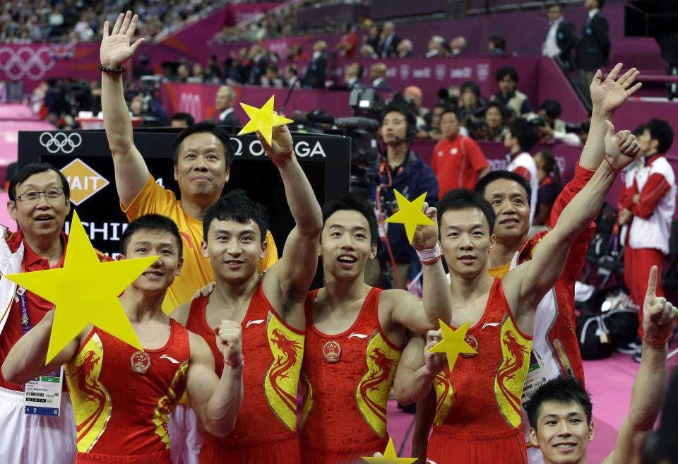 The Chinese team hold up cutouts of gold stars as they celebrate their gold medal in the Artistic Gymnastic men's team final at the 2012 Summer Olympics, Monday, July 30, 2012, in London. (AP Photo/Julie Jacobson)