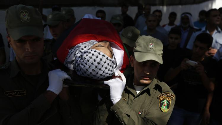 Palestinian security forces carry the body of Mahmoud al-Shawamrah during his funeral in Al-Ram