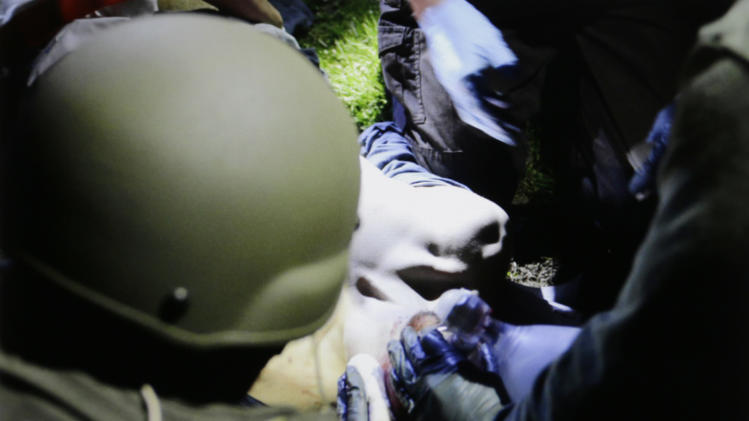 In this Friday, April 19, 2013 Massachusetts State Police photo, tactical emergency medical technicians tend to 19-year-old Boston Marathon bombing suspect Dzhokhar Tsarnaev at the time of his capture by law enforcement authorities in Watertown, Mass. (AP Photo/Massachusetts State Police, Sean Murphy)