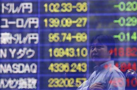 A man is reflected in an electronic board showing exchange rates in Tokyo