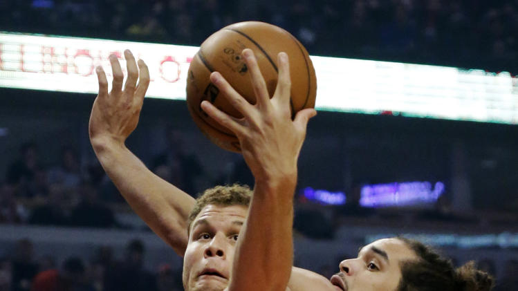 Los Angeles Clippers forward Blake Griffin, left, grabs a rebound over Chicago Bulls center Joakim Noah during the first half of an NBA basketball game, Tuesday, Dec. 11, 2012, in Chicago. (AP Photo/Charles Rex Arbogast)