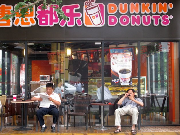 SHANGHAI, CHINA - JULY 7: American donut chain Dunkin&#39; Donuts now has 40 outlets around China, including 18 here in Shanghai, with ambitious plans to expand to 100 stores in China within the decade.&Acirc;&nbsp; Shanghai is in the midst of what has been called &quot;the donut wars,&quot; as Dunkin&#39; faces competition from Krispy Kreme, Mister Donut, Donut King, and a host of other local shops, all for the morning palates of Shanghai&#39;s increasingly affluent young consumers.&Acirc;&nbsp; What&#39;s not clear is whether sweet American-style donuts are popular in China, where morning breakfast generally consists of congee, or rice porridge, soybean milk, and maybe a plain, steamed bun.&Acirc;&nbsp;&Acirc;&nbsp; Here, two men relax in the shade on benches outside a Dunkin&#39; Donuts outlet.(Photo by Keith B. Richburg/The Washington Post via Getty Images)