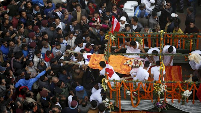 People gather around the body of former Prime Minister Sushil Koirala during his funeral procession in Kathmandu