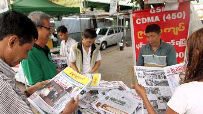 In this Nov. 20, 2012, photo, people browse local weekly news journals reporting U.S. President Barack Obama's trip to Myanmar at a newsstand, in Yangon, Myanmar. Little noticed during Obama's landmark visit to Myanmar was a significant concession that could shed light on whether that nation's powerful military pursued a clandestine nuclear weapons program, possibly with North Korea's help. Myanmar announced it would sign an international agreement that would require it to declare all nuclear facilities and materials. Although it would be up to Myanmar to decide what to declare, it could provide some answers concerning its acquisition of dual-use machinery and military cooperation with North Korea. (AP Photo/Khin Maung Win)