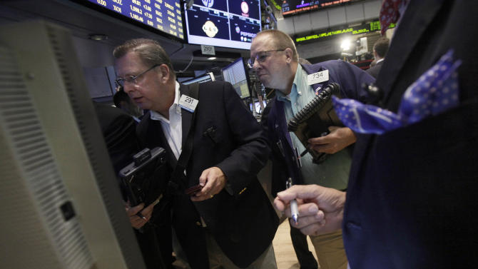 FILE- In this Friday, Aug. 3, 2012, file photo, traders work on the floor of the New York Stock Exchange. Stocks closed lower Thursday, Aug. 30, 2012, with investors too worried about gas prices and unemployment to be impressed by news that consumer spending is up. (AP Photo/Richard Drew, File)