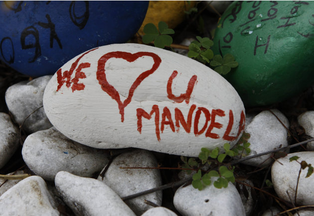 A pebble with a message to former President Nelson Mandela lays outside his Johannesburg home Thursday, Dec. 27 2012. Mandela was released Wednesday from the hospital after being treated for a lung in