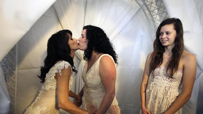 Grace Meier, right, watches her mother Sallee Taylor, center, and partner Andrea Taylor during a wedding ceremony in West Hollywood, Calif., Monday, July 1, 2013. The city of West Hollywood is offering civil marriage ceremonies for same-sex couples free of charge Monday. (AP Photo/Jae C. Hong)