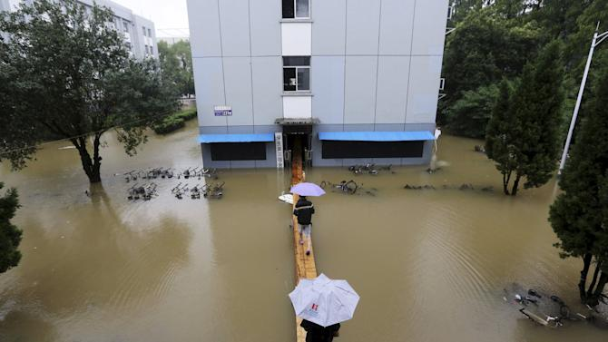 Students walk on a makeshift bridge as they enter their dormitory building which is partially submerged by floodwater, at university campus after heavy rainfall hit Nanjing