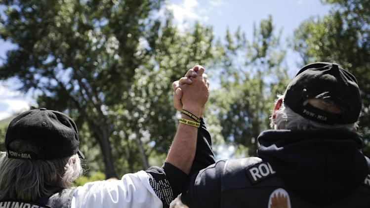 "Two Vietnam War veterans, Bill Sharpness, left, and Bill Atkinson hold in hands as they sing ""God Bless America"" at the ""Bring Bowe Back"" celebration held to honor captive U.S. Army Sgt. Bowe Bergdahl in Hailey, Idaho, Saturday, June 22, 2013. Hundreds of activists for missing service members gathered in a small Idaho town Saturday to hear the parents of the only known U.S. prisoner of war speak just days after his Taliban captors announced they want to exchange him for prisoners being held at Guantanamo Bay. (AP Photo/Jae C. Hong)"
