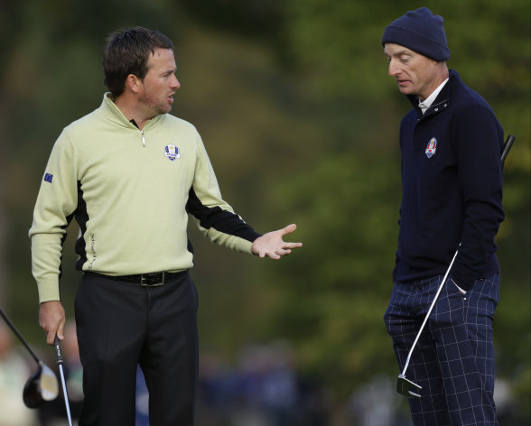 Europe's Graeme McDowell, left, and USA's Jim Furyk talk about getting relief during a foursomes match at the Ryder Cup PGA golf tournament Friday, Sept. 28, 2012, at the Medinah Country Club in Medinah, Ill. (AP Photo/David J. Phillip)