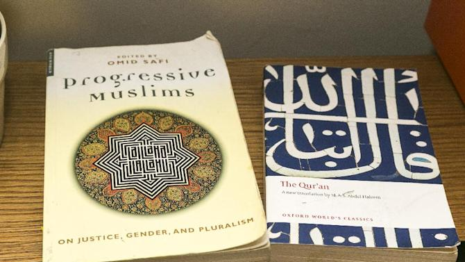 American Muslim Omar Akersim's books the Progressive Muslim is viewed next to The Quran, the Muslim holy book at his home in Los Angeles Friday, Aug. 1, 2014. Nearly 40 percent of the estimated 2.75 million Muslims in the U.S. are American-born and the number is growing, with the Muslim population skewing younger than the U.S. population at large, according to a 2011 survey by the Pew Research Center. (AP Photo/Damian Dovarganes)