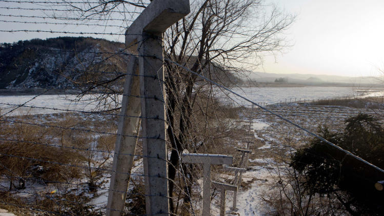 In this Saturday, Dec. 8, 2012 photo, a bard wire fence along the Chinese border looks into North Korea near the Chinese border town of Tumen in eastern China's Jilin province. Over the past year, Kim Jong Un has intensified a border crackdown that has attempted to seal the once-porous 1,420-kilometer (880-mile) frontier with China, smugglers and analysts say, trying to hold back the onslaught.(AP Photo/Ng Han Guan)