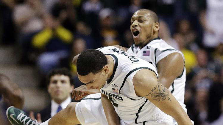 Michigan State guard Denzel Valentine, left, and forward Adreian Payne celebrate against Memphis in the second half of their third-round game of the NCAA college basketball tournament in Auburn Hills, Mich., Saturday March 23, 2013. Michigan State won 70-48. (AP Photo/Paul Sancya)