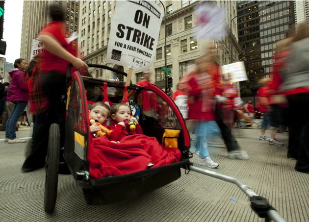 Two-year-old identical twins Colton and Lucas Jordan join thousands of public school teachers and their supporters as they march along Chicago's Michigan Avenue, protesting against Penny Pritzker, who