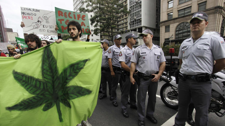 Demonstrators hold an image of a cannabis leaf as police stand guard during a march in favor of the legalization of marijuana in Sao Paulo, Brazil, Saturday July 2, 2011. The Brazilian Supreme Court ruled on June 15, 2011 that demonstrations favoring the legalization of cannabis are an exercise of free expression and do not encourage people to consume it. (AP Photo/Nelson Antoine)
