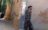 "Syrian government soldiers patrolling in Damascus on July 31. Clashes erupted near two Christian areas of the Syrian capital Wednesday for the first time in the nearly 17-month uprising, as the battle for Aleppo entered its fifth day and President Bashar al-Assad hailed the ""heroic"" army"