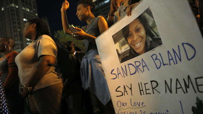 A demonstraor holds a Sandra Bland sign during a vigil, Tuesday evening, July 28, 2015,  near the DuSable Bridge on Michigan Ave. in Chicago. Bland died in a Texas county jail after the traffic stop for failing to use a turn signal escalated into a physical confrontation. Authorities have said Bland hanged herself, a finding her family disputes. The death has garnered national attention amid increased scrutiny of police treatment of blacks in the wake of several high-profile police-involved deaths. (AP Photo/Christian K. Lee)