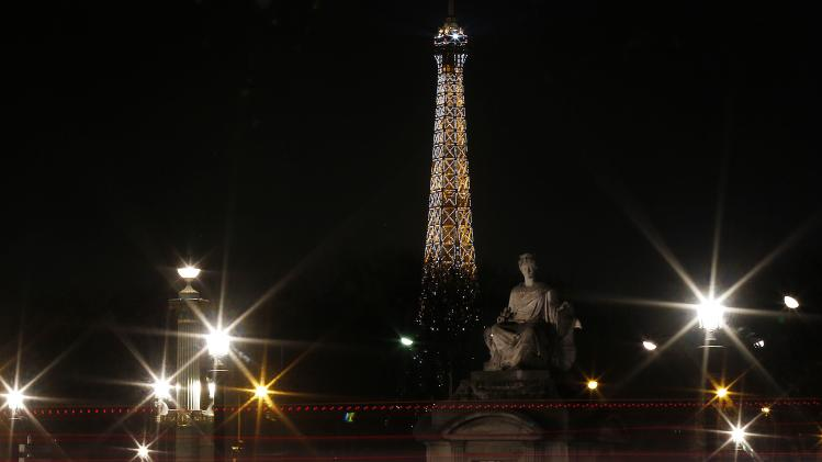 The Eiffel tower which lights up the night sky is seen from the Place de la Concorde square in Paris