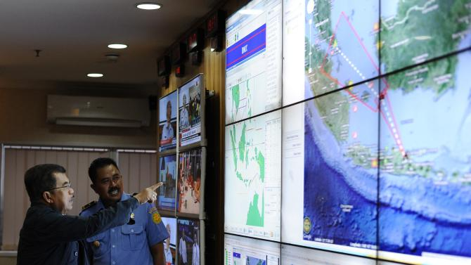 Indonesia's vice-president Jusuf Kalla monitors progress in search for AirAsia Flight QZ8501 during a visit to the National Search and Rescue Agency in Jakarta