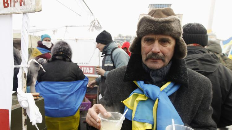 A protester carries free soup at Independence square in Kiev
