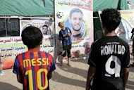 Palestinian boys play football in front of posters showing solidarity with Mahmud Sarsak in Rafah town in the southern Gaza Strip. Sarsak is a football player from the Gaza Strip and was detained by Israeli troops while traveling to play with Palestinian team in the Israeli occupied West Bank. AFP PHOTO / SAID KHATIB