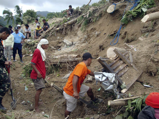 In this Tuesday Feb.7, 2012 photo, rescuers and residents search for survivors following a landslide triggered by a Magnitude 6.9 earthquake at Guihulngan township, Negros Oriental province in central