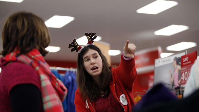 In this November 2014 photo, employee Jen Sans points a customer in the right direction at a Target store, in South Portland, Maine. The National Retail Federation found in a survey that only 9 percent of shoppers finished their shopping by the start of December this year and nearly 15 percent hadn't even started. (AP Photo/Robert F. Bukaty)