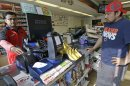 A customer, right, waits for his Powerball lottery ticket at a convenience store in Chicago on Saturday, May 18, 2013. A little more than a year after three tickets split a world-record lottery prize, the jackpot for Saturday&#039;s Powerball drawing was nearing historic territory. Should nobody pick the correct six numbers, the prize money will roll over to next week&#039;s drawing and almost certainly eclipse the $656 million doled out to winners in Illinois, Kansas and Maryland in the Mega Millions game in March 2012. (AP Photo/Nam Y. Huh)