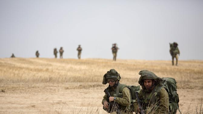 CORRECTS BYLINE - Israeli soldiers march during a drill near the Israel and Gaza border, Tuesday, July 22, 2014. Israeli airstrikes pummeled a wide range of locations in the Gaza Strip on Tuesday as the U.N. chief and the U.S. secretary of state began an intensive effort to end more than two weeks of fighting that has killed hundreds of Palestinians and dozens of Israelis.(AP Photo/Dusan Vranic)