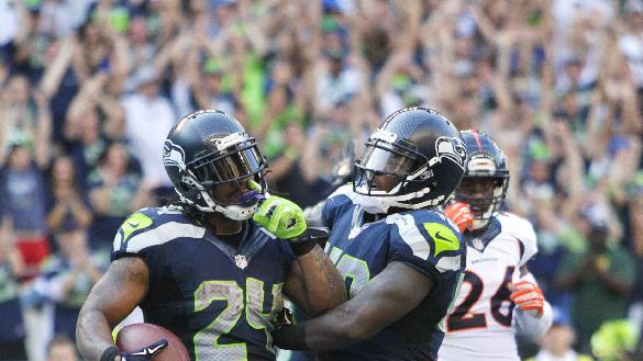 Seattle Seahawks running back Marshawn Lynch (24) celebrates with Derrick Coleman after Lynch scored the game-winning touchdown in overtime of an NFL football game against the Denver Broncos, Sunday, Sept. 21, 2014, in Seattle. The Seahawks won 26-20