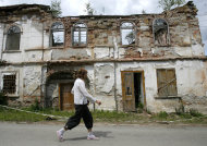 In this photo taken Sunday, Aug. 14, 2011, a woman walks past an old building in the Transylvanian mining city of Rosia Montana, Romania. With the precious metal at an all-time high, a Canadian company is eager to start blasting out mountains and demolishing parts of this ancient town to build an open-cast mine where 300 tons of gold and 1,600 tons of silver are buried. The plan, which would use cyanide in the extraction process, faces fierce opposition from ecologists and many locals who want to preserve the region's unique heritage. (AP Photo/Nicolae Dumitrache)