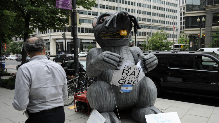 COMMERCIAL IMAGE - In this photo taken by AP Images for American Task Force Argentina, an onlooker looks at a large inflatable rat standing near the Inter-American Development Bank, Monday, May 7, 2012, in Washington. The rat greeted Argentine Vice President Amado Boudou's visit at the Council of the Americas reception at the bank. The rat also calls for Argentina's expulsion from the G-20. Protestors demanded that Argentina abide by its obligations to U.S. investors and to the rule of law internationally. (Nick Wass/AP Images for American Task Force Argentina )