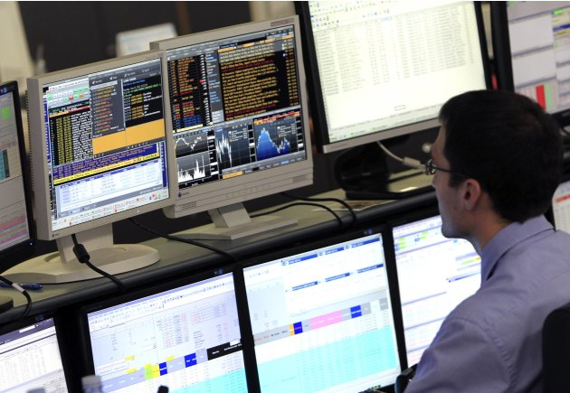 A trader looks at his screens on the Unicredit Bank trading floor in downtown Milan