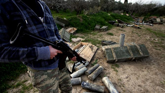 In this Thursday, Feb. 21, 2013 photo, a Free Syrian army fighter stands guard in the backyard of the Santa Ana Armenian Orthodox church, which was used as a shelling base by Syrian army forces, at the Christian village of Yacobiyeh, in Idlib province, Syria. Yacobiyeh and its neighbors, Judeida and Quniya, are some of the first Christian villages to be taken by the rebel Syrian Army. The rebels stormed these hilltop villages in late January, after the army used it as a base to shell nearby rebel-controlled areas. The villages are largely empty due to the fighting, with a few mostly elderly Christians -- including Roman Catholics and Armenian Orthodox _ living among Sunni Muslim refugees who have moved up here from the plains. They still face sporadic artillery bombardment from below.(AP Photo/Hussein Malla)