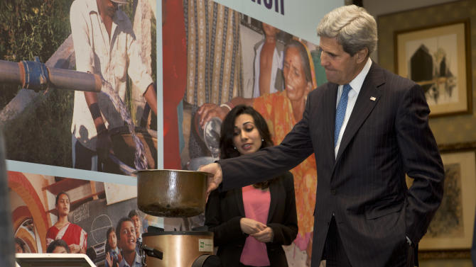 """U.S. Secretary of State John Kerry, right, talks with Neha Juneja, co-founder and CEO of Greenway Grameen Infra, about her generators based on low-cost thermoelectric modules that generate electricity from widely used biomass stoves during cooking, during a tour of exhibits called """"Green and Affordable Innovation"""" in New Delhi, India on Monday, June 24, 2013. (AP Photo/Jacquelyn Martin, Pool)"""