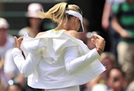 Russia's Maria Sharapova takes off her training top before her match against Bulgaria's Tsvetana Pironkova on Thursday. Sharapova had crushed Anastasia Rodionova in the first round in her first match since winning the French Open earlier this month, but Pironkova made the Russian fight far harder to keep her title bid on course
