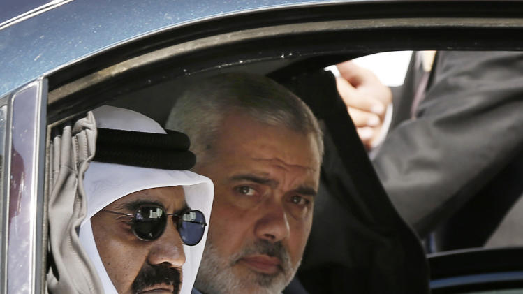Emir of Qatar Sheikh Hamad bin Khalifa al-Thani, left, and Gaza's Hamas prime minister Ismail Haniyeh, right, arrive for the corner-stone laying ceremony for Hamad, a new residential neighborhood in Khan Younis, southern Gaza Strip Tuesday, Oct. 23, 2012. The emir of Qatar received a hero's welcome in Gaza on Tuesday, becoming the first head of state to visit the Palestinian territory since the Islamist militant Hamas seized control there in 2007. (AP Photo/Mohammed Salem, Pool)