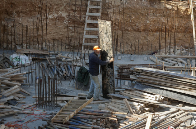 A Palestinian worker is seen on a construction site in the east Jerusalem neighborhood of Ramat Sholmo, Tuesday, Dec. 18, 2012. A European diplomat says Germany and three other European members of the U.N. Security Council are preparing a statement condemning Israel's latest settlement plans in the West Bank.(AP Photo/Dan Balilty)