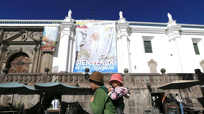 A woman holding her baby walks by a banner of Pope Francis' upcoming visit to the country at the main square in Quito
