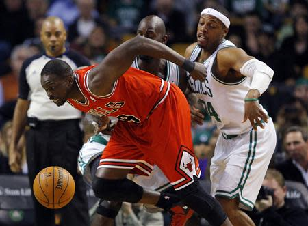 Chicago Bulls' Deng breaks through the defense of Boston Celtics' Garnett and Pierce in their NBA basketball game in Boston