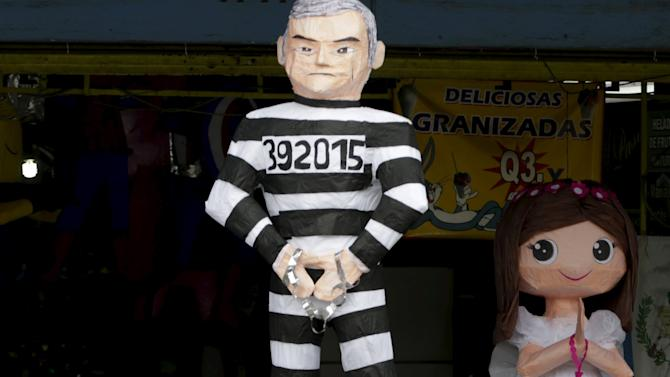 A man walks past a pinata representing former Guatemala's President Otto Perez wearing a jail uniform outside a pinatas store in downtown Guatemala City