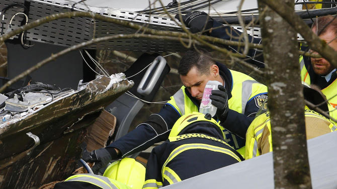 Rescue personnel attend an injured person beside of two trains that collided head-on near Bad Aibling, southern Germany, Tuesday, Feb. 9, 2016. Several people have been killed and dozens were injured. (AP Photo/Matthias Schrader)